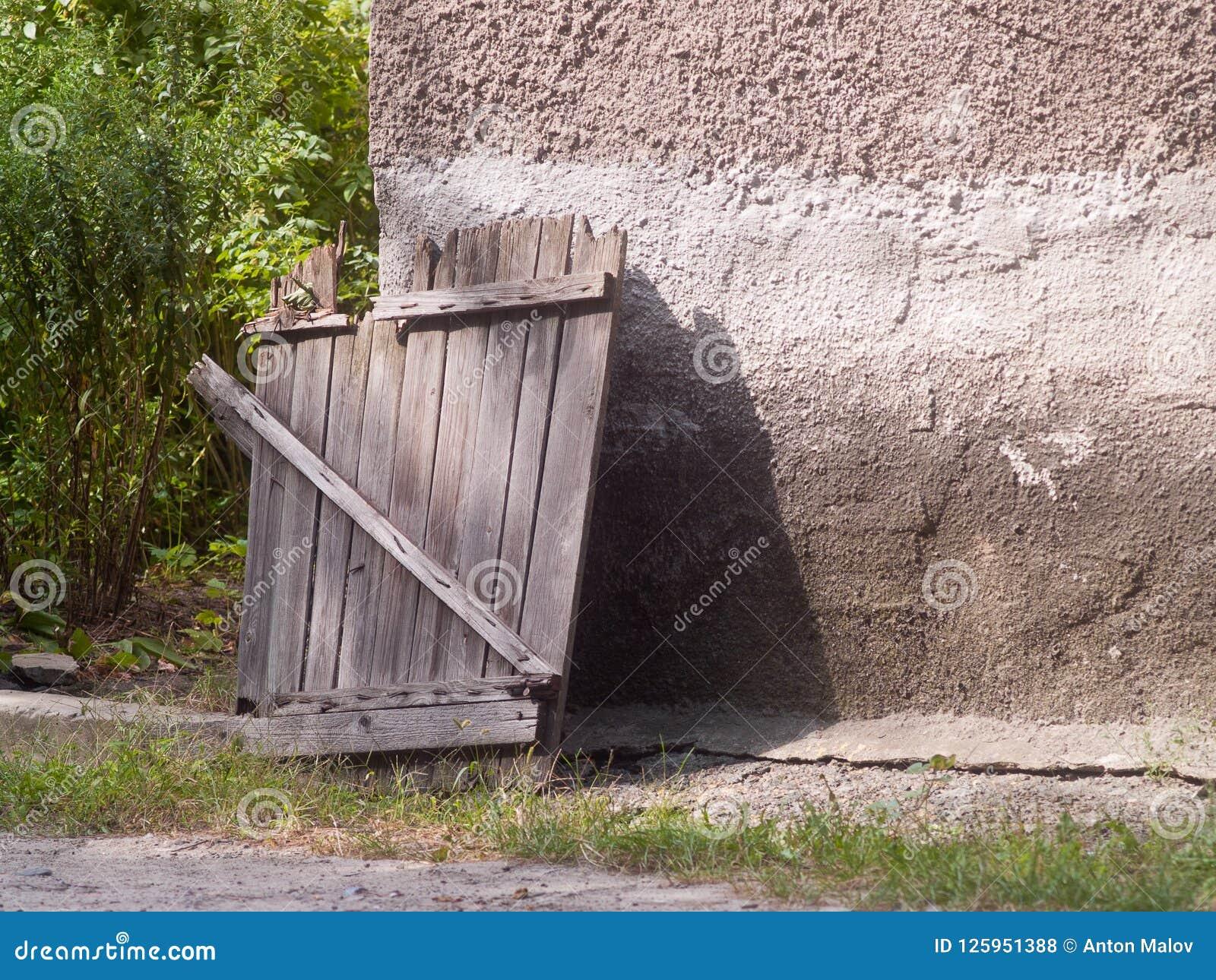 Vieille porte en bois ouverte au jardin