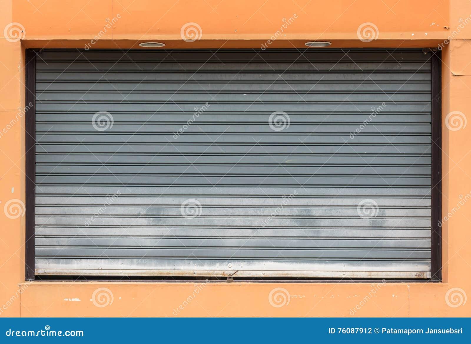 Vieille porte grise de volet de rouleau