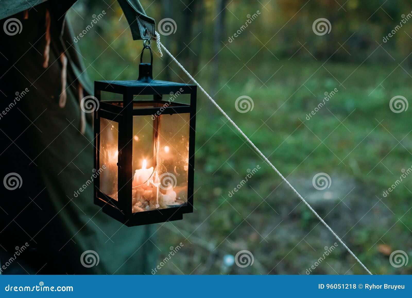 Vieille rétro lanterne de vintage avec la bougie brûlante accrochant sur la tente de camp