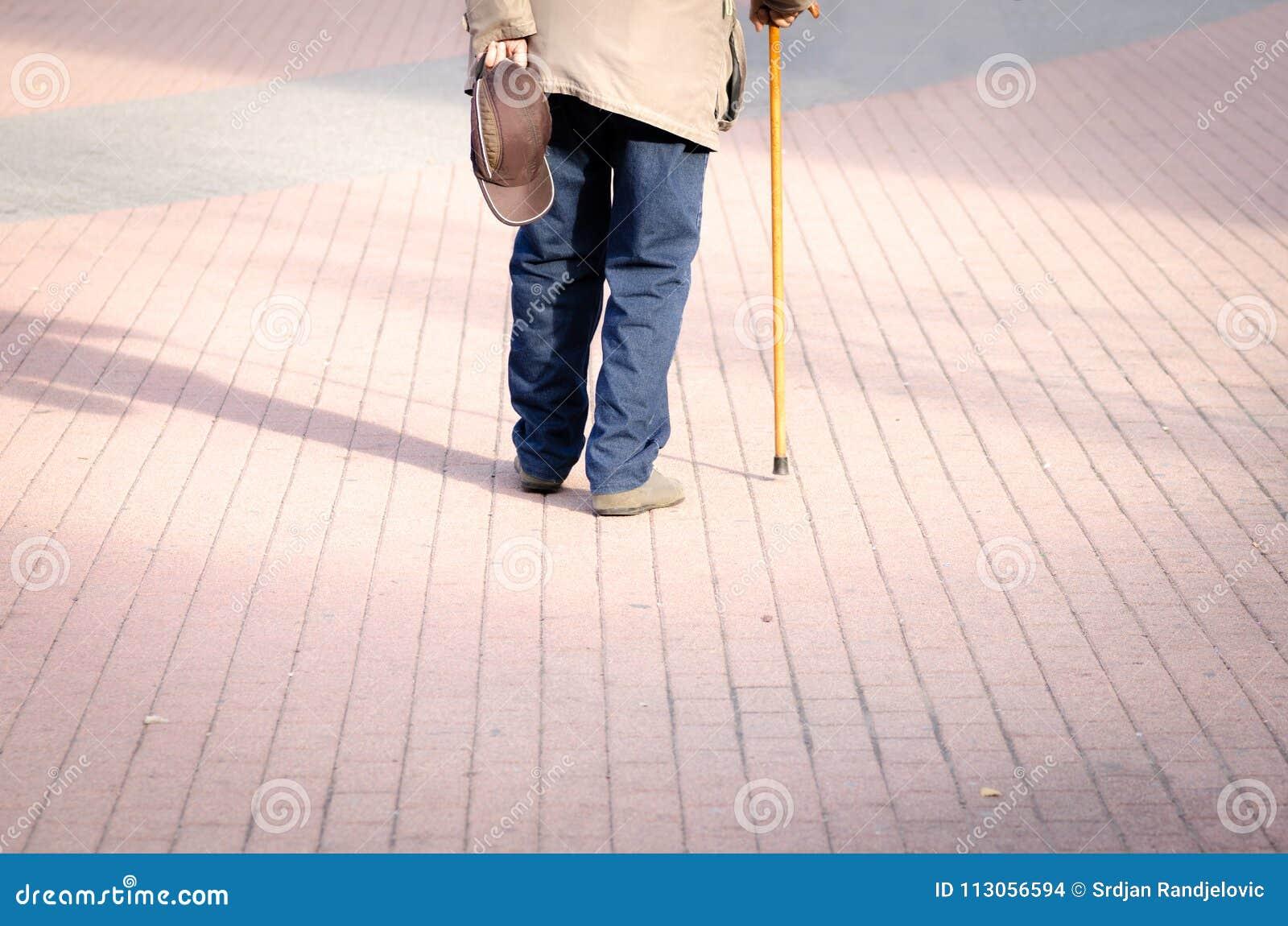 Vieille seule promenade déprimée d homme en bas de la rue avec la vue isolée et perdue de sentiment de bâton ou de canne de march