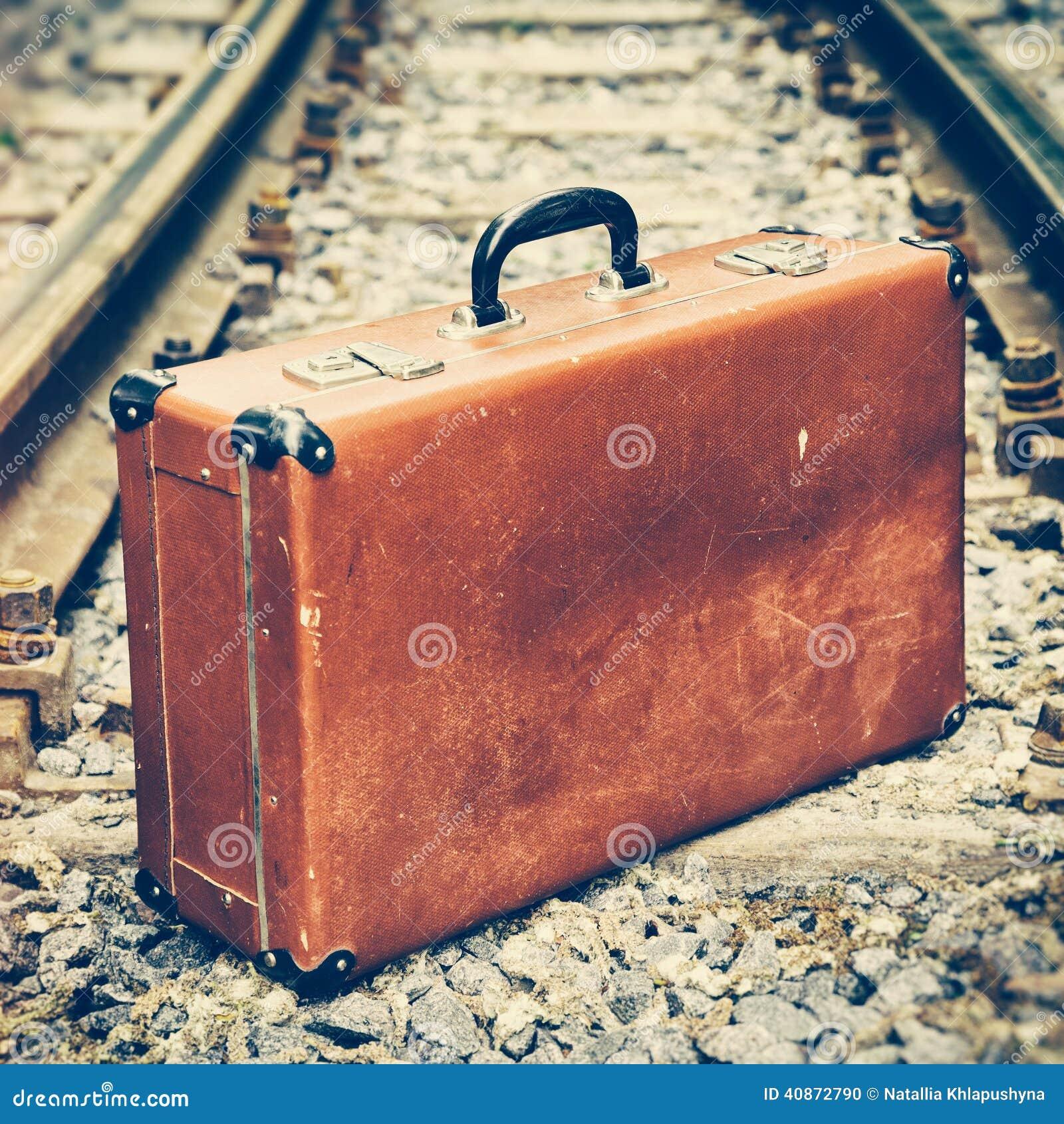 Vieille valise sur le chemin de fer