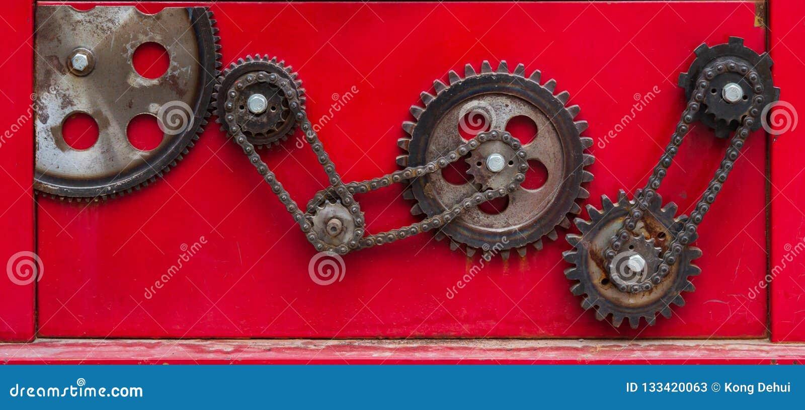 Vieille vitesse à chaînes rouillée sur un backgro rouge
