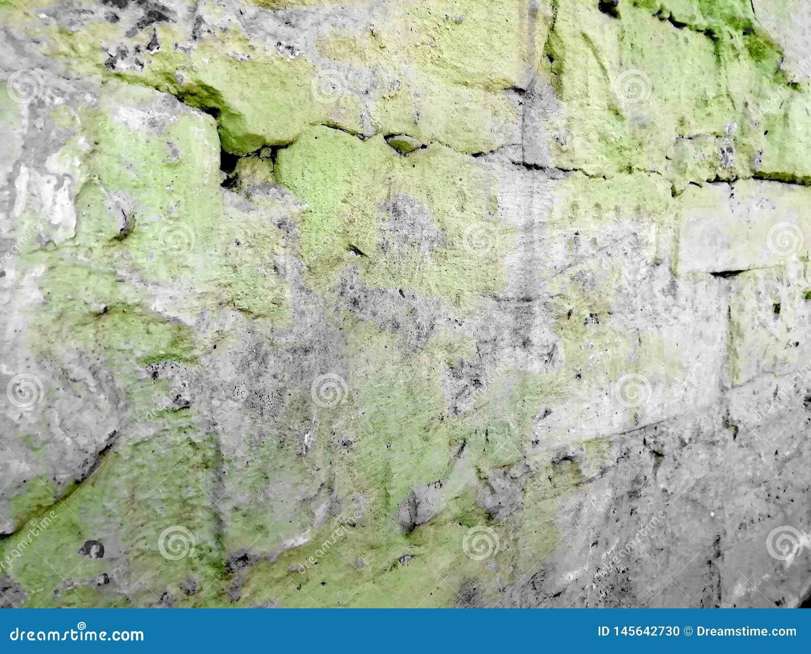 Vieilles briques en peinture verte avec des crevasses avec les taches grises
