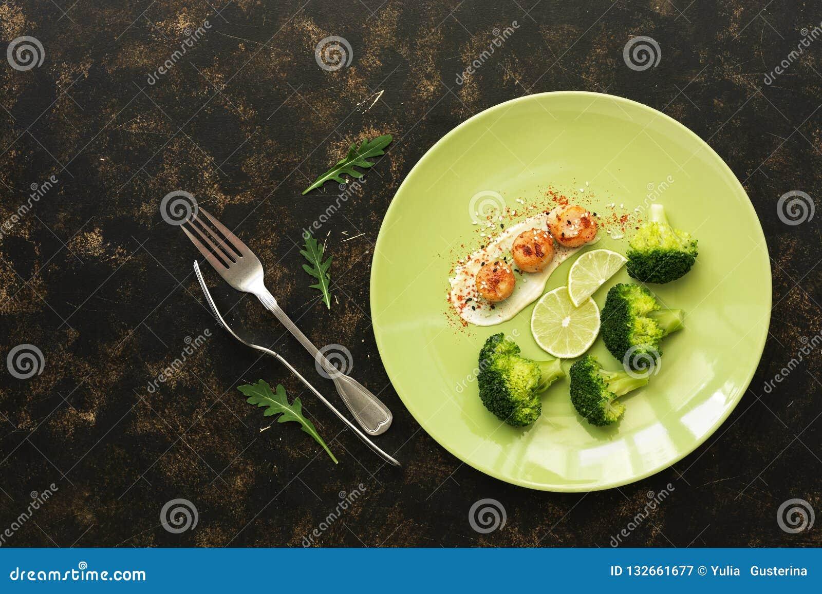 Vieiras com brócolis e cal em uma placa em um fundo rústico escuro delicacy Alimento da dieta saudável Vista superior, configuraç