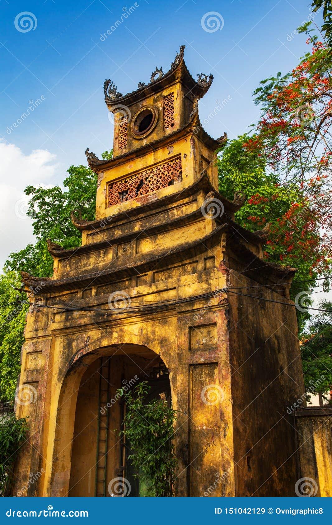 Vieja puerta amarilla alta rodeada por los árboles en la ciudadela larga de Thang en la ciudad imperial, Hanoi, Vietnam