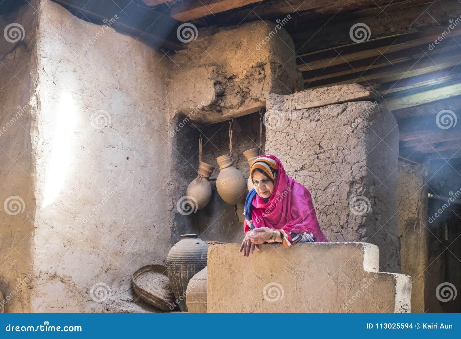 Vieja señora omaní que descansa en una cocina tradicional vieja