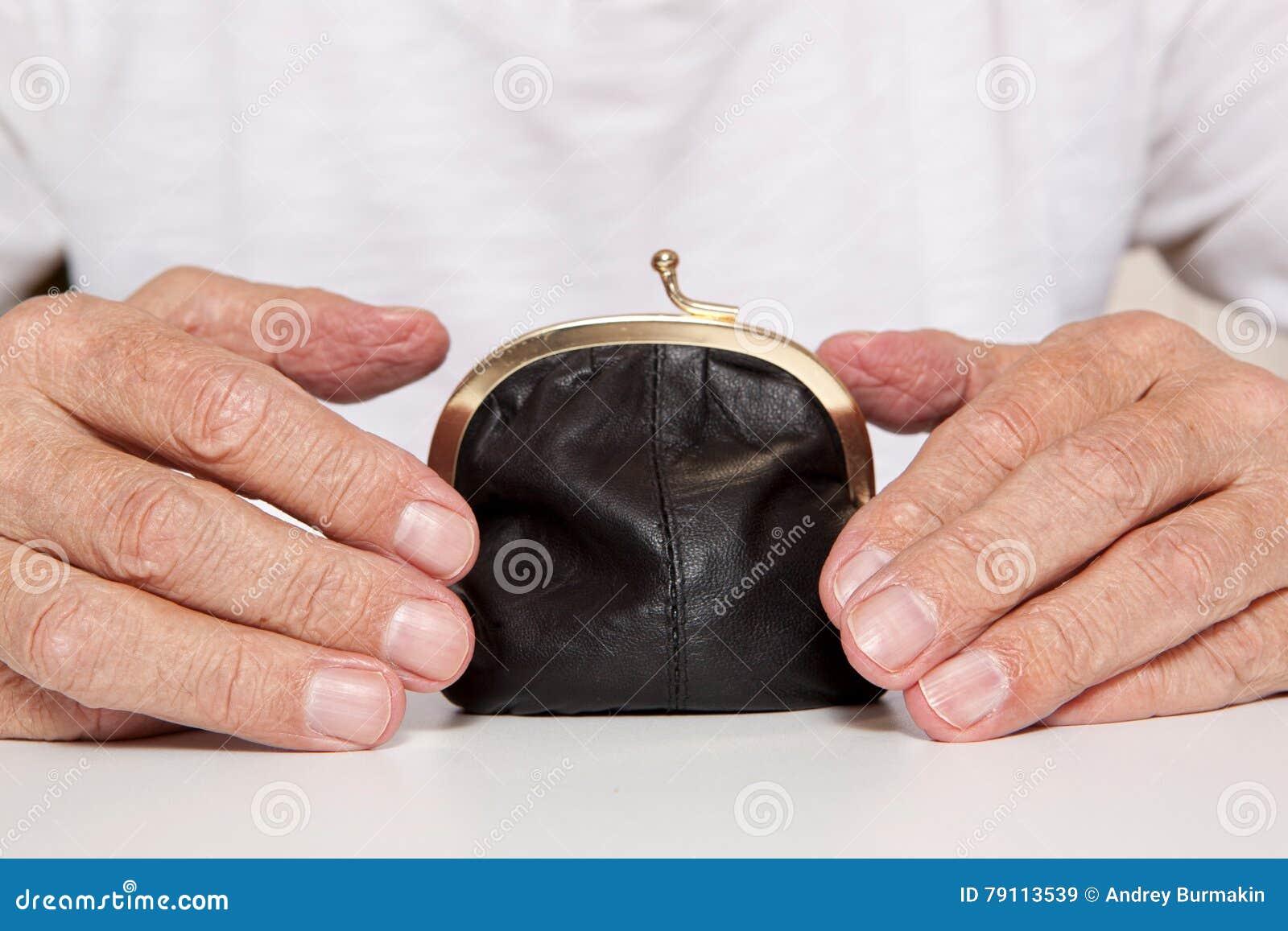 Viejas manos mayores y pequeña bolsa del dinero