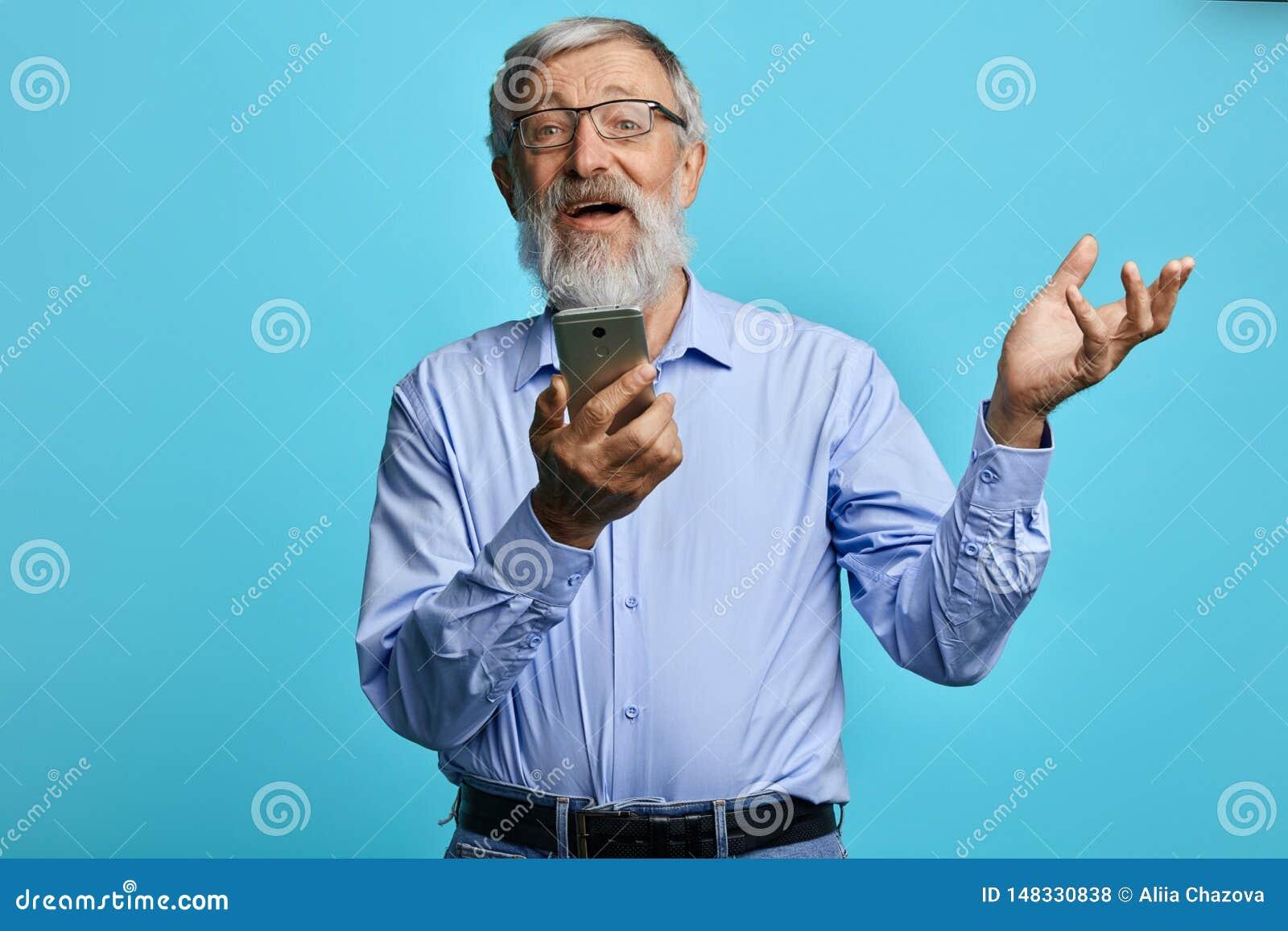 Viejo hombre alegre con la mano aumentada que sostiene el teléfono móvil