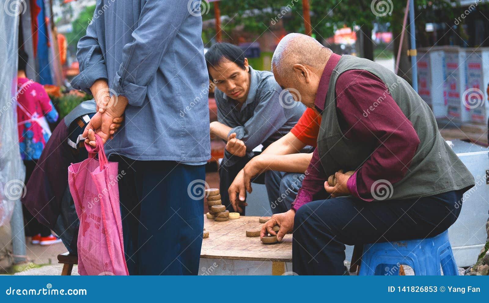 Viejo hombre asiático que juega a ajedrez
