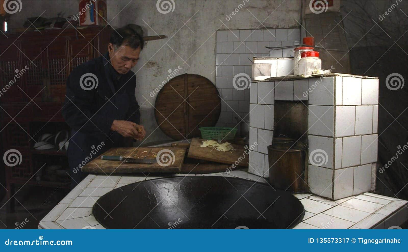 Viejo hombre chino que cocina en cocina en su campo casero yunnan China