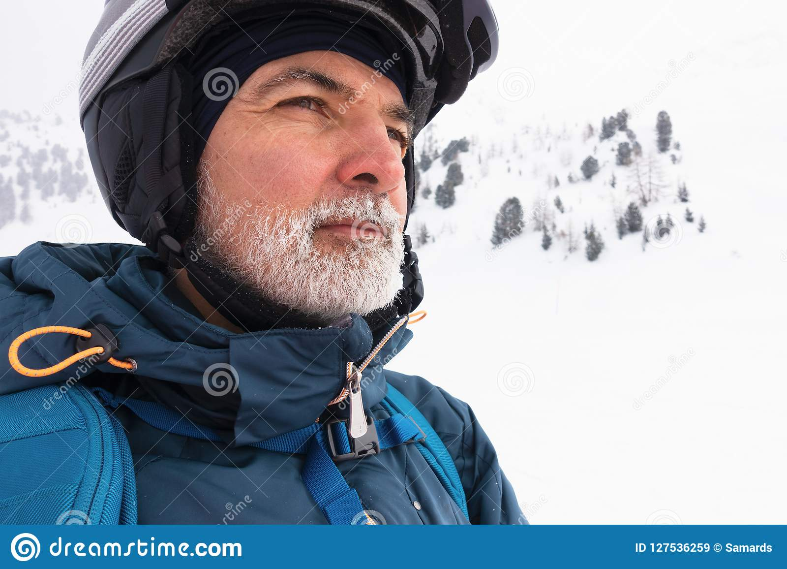 Viejo hombre con la barba blanca en la montaña nevosa