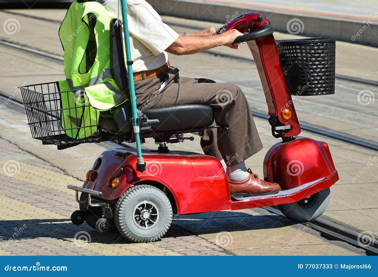 Viejo hombre con una silla de ruedas el ctrica foto de archivo imagen 77037333 - Silla de ruedas electrica usada ...