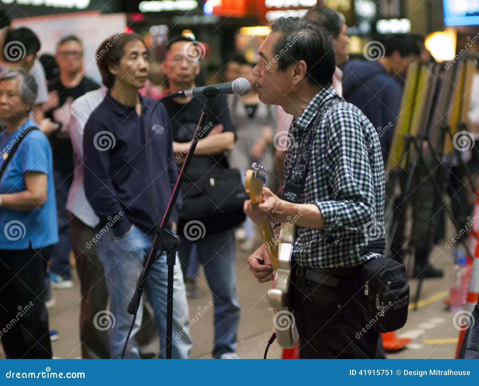 Viejo hombre de Hong Kong que toca la guitarra en la calle