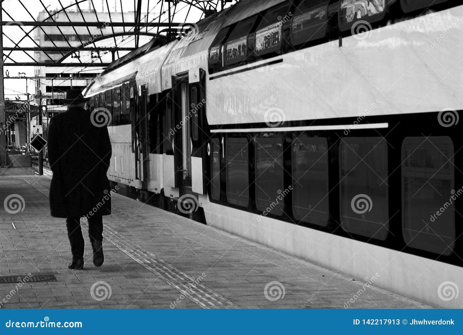 Viejo hombre que camina a lo largo de un tren de una plataforma vacía que está viajando o dijo adiós alguien - BW