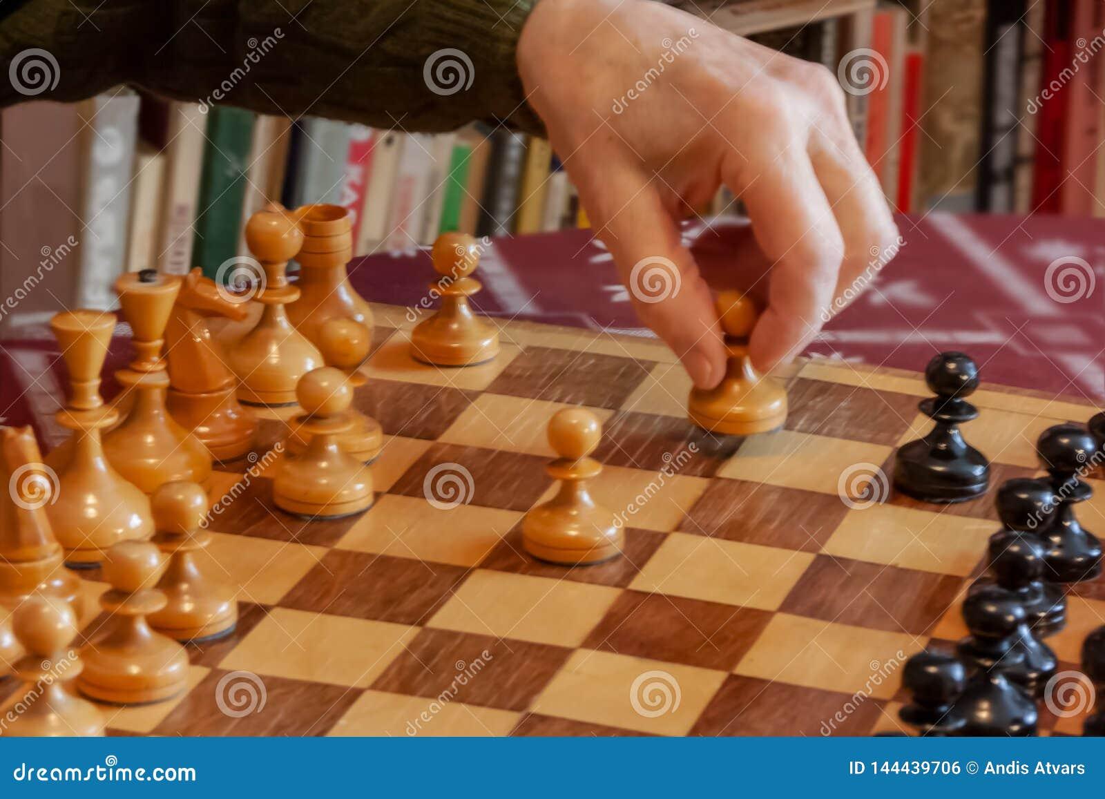 Viejo hombre que juega al ajedrez, mano que sostiene el empeño