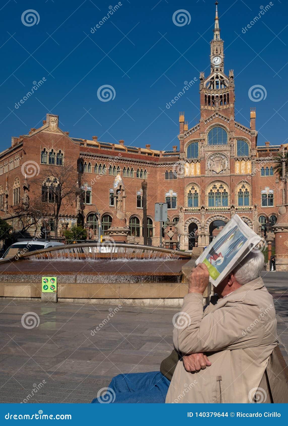 Viejo hombre que se sienta en banco cerca del edificio hermoso de Sant Pau Hospital en Barcelona, Cataluña, España