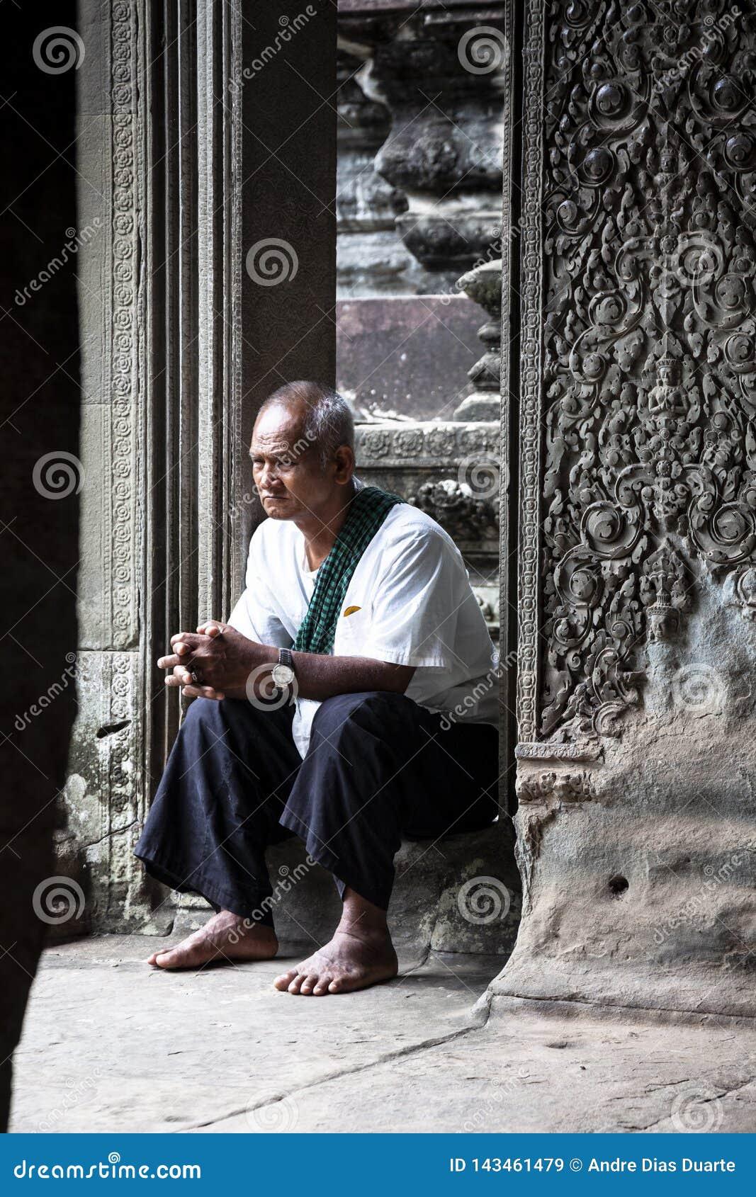 Viejo hombre que se sienta en un templo de piedra