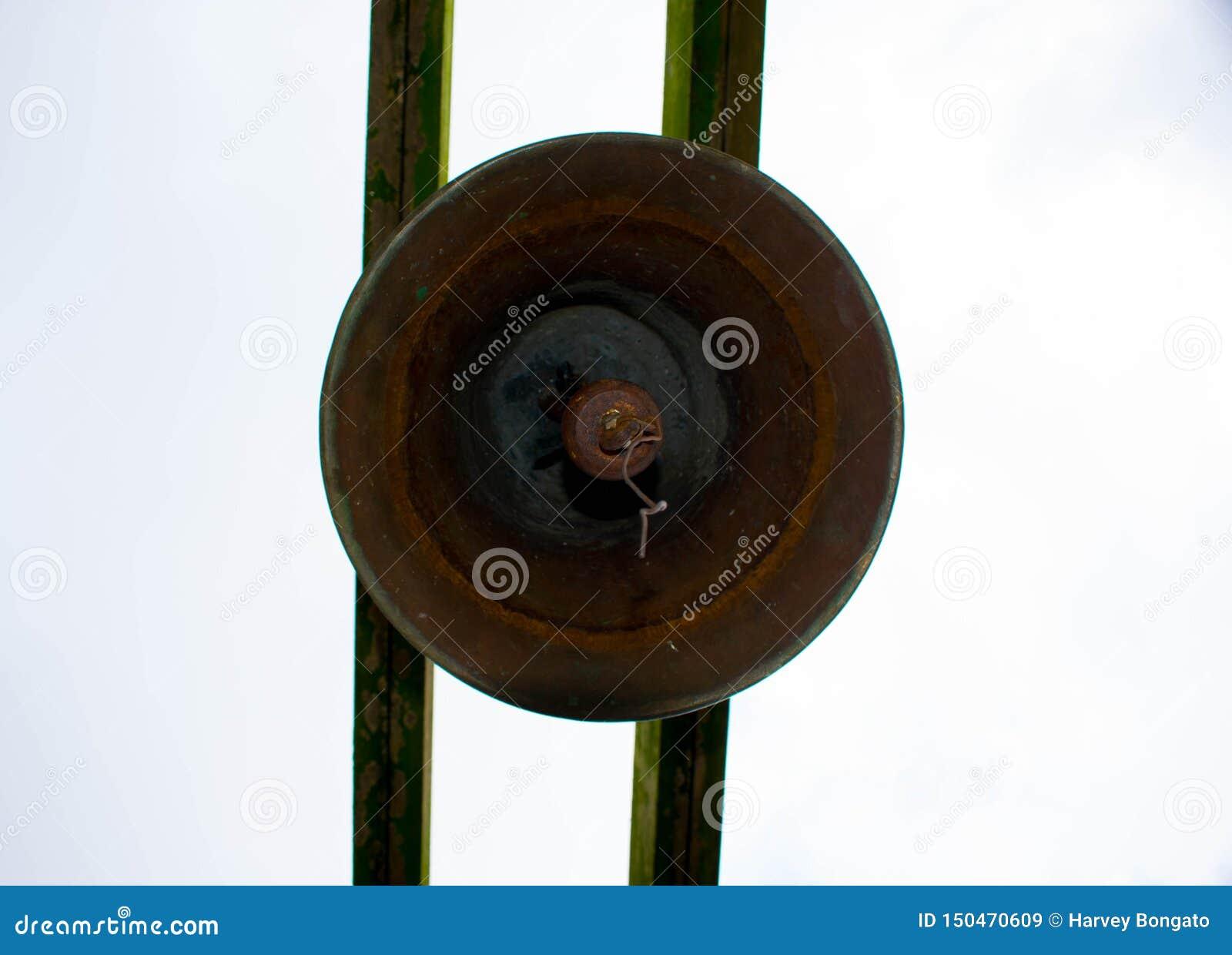 Viejo Rusty Bronze Bell Hanged en el tablón de madera cubierto de musgo dos
