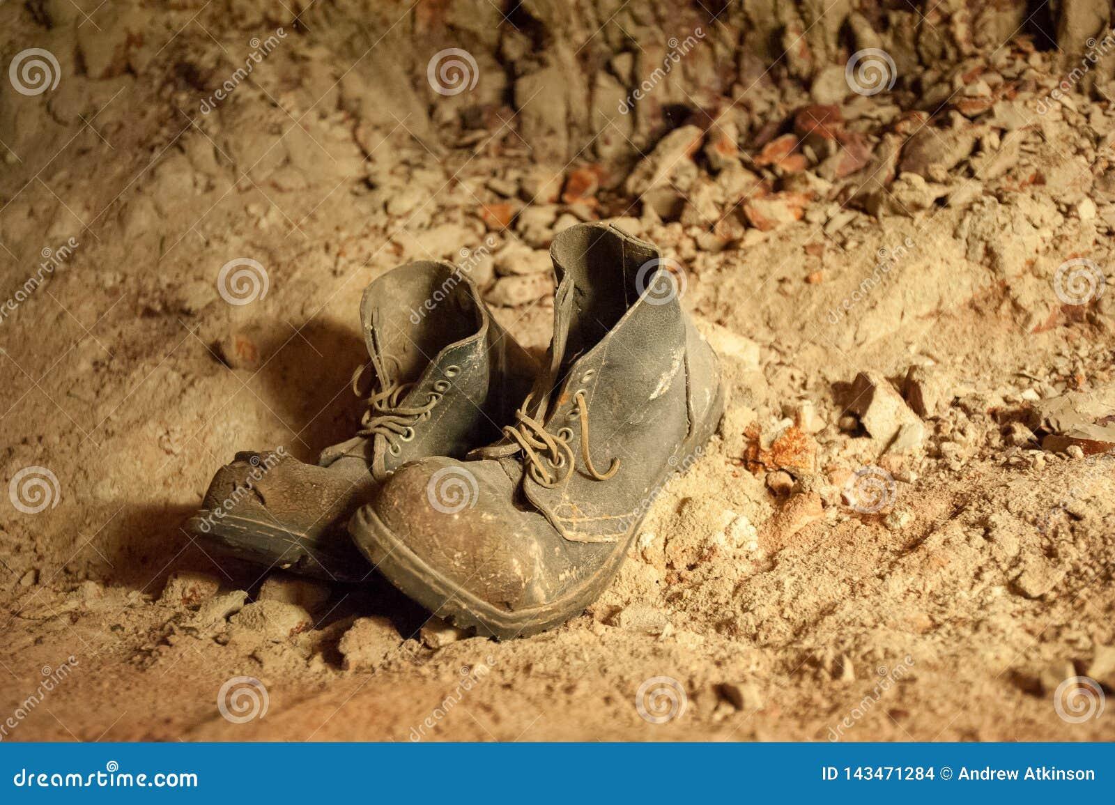 Viejos pares de botas desechadas con los cordones