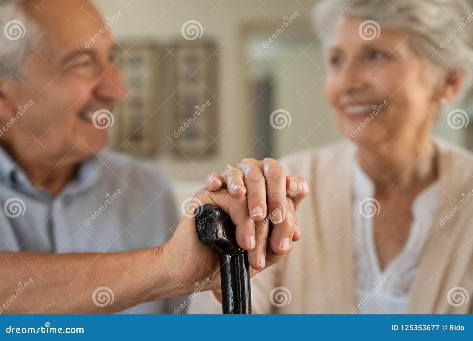 Viejos pares felices que sostienen el bastón