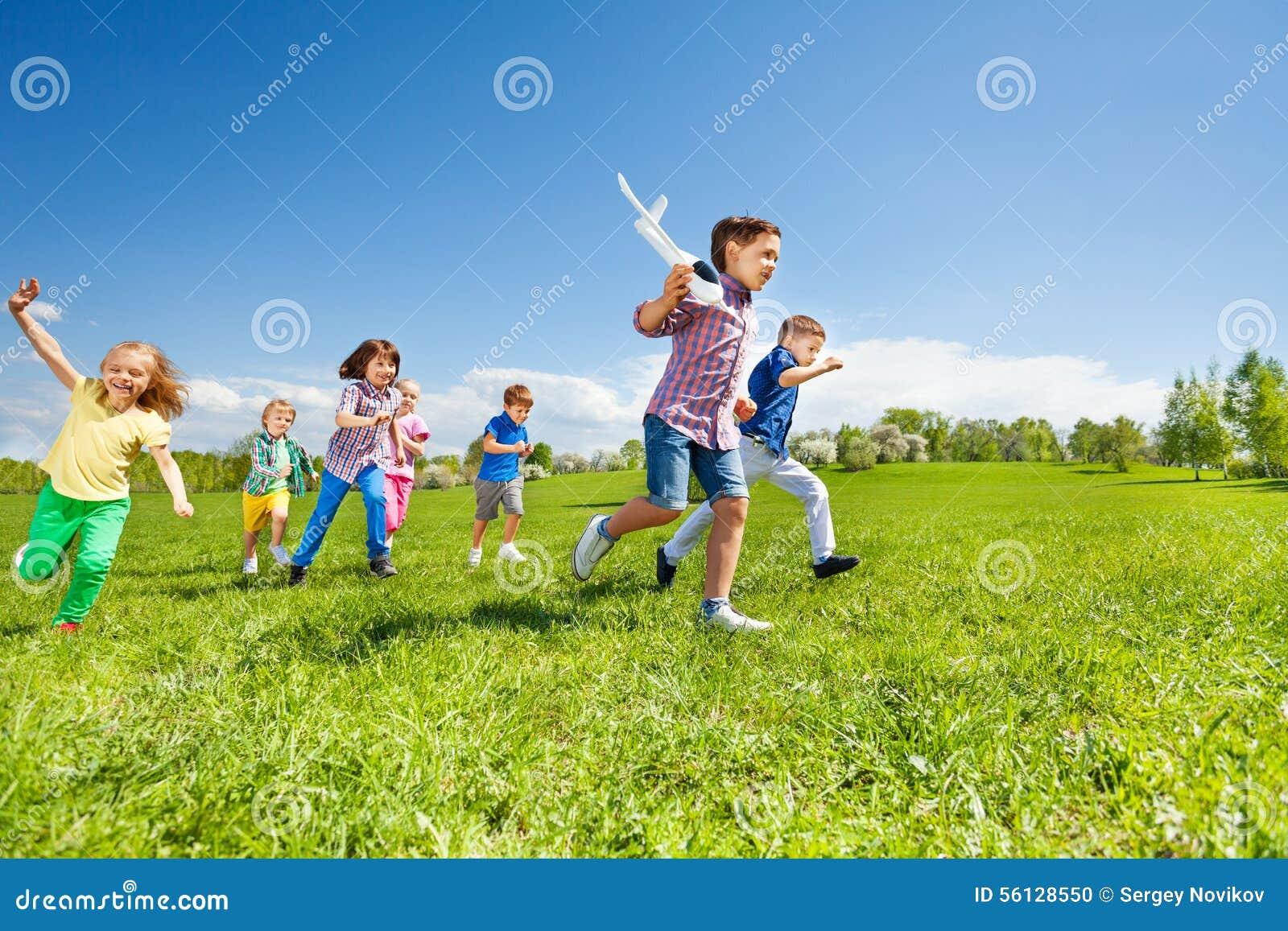 Viel Kinderlaufen und -junge Flugzeugspielzeug halten