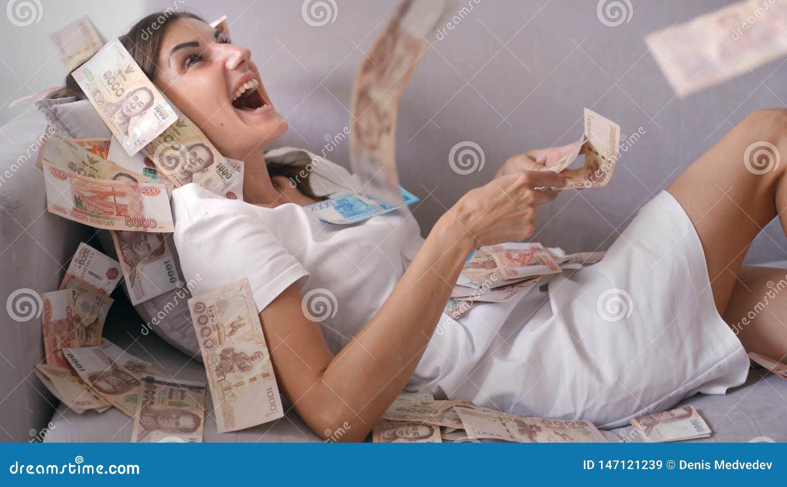 Viele Banknoten fliegen in die Luftunkosten in der Zeitlupe Ein M?dchen liegt und viele Geldf?lle auf sie gl?ckliche Frau freut s