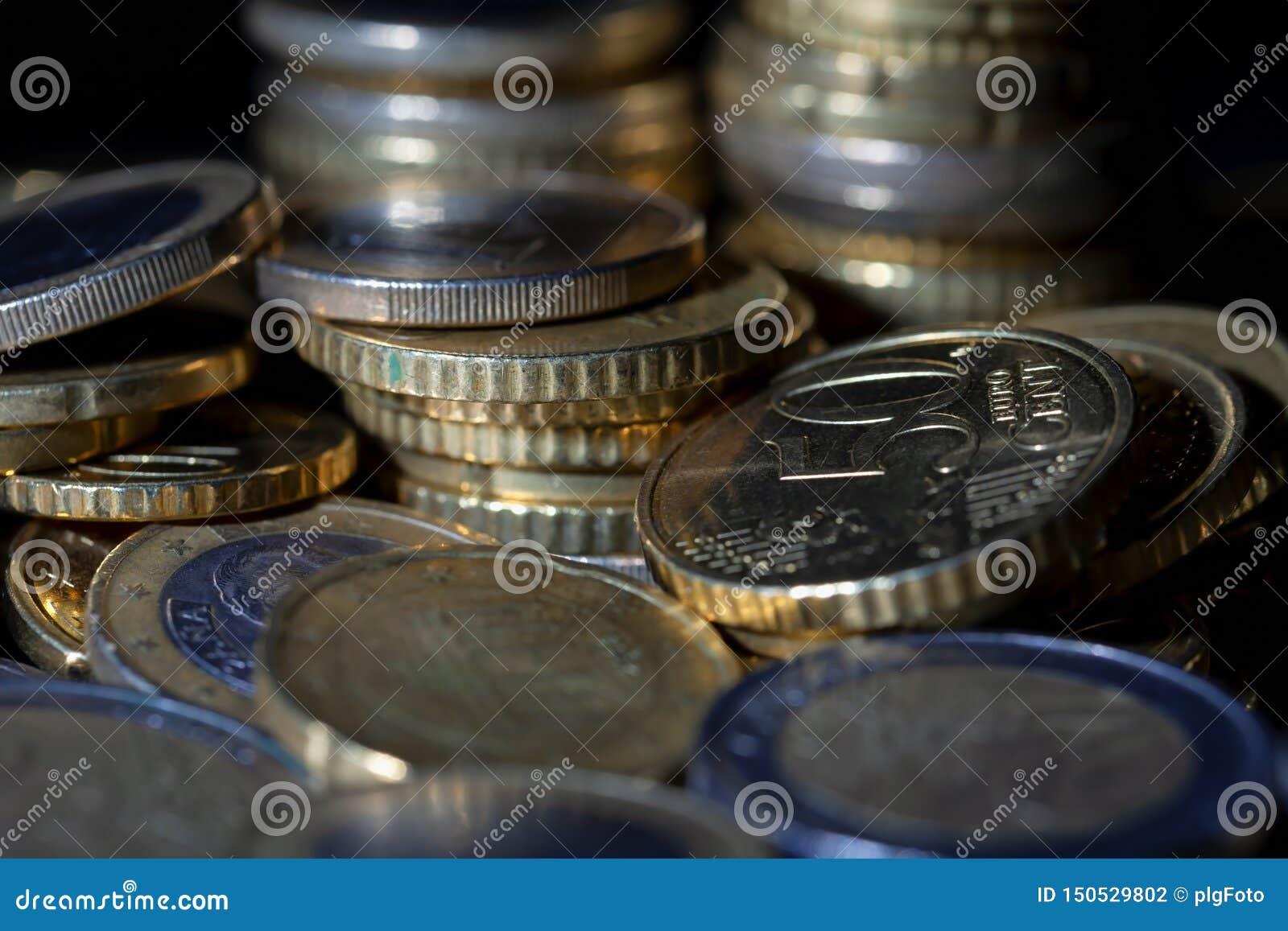 Viele Euromünzen und Cents auf Schwarzem
