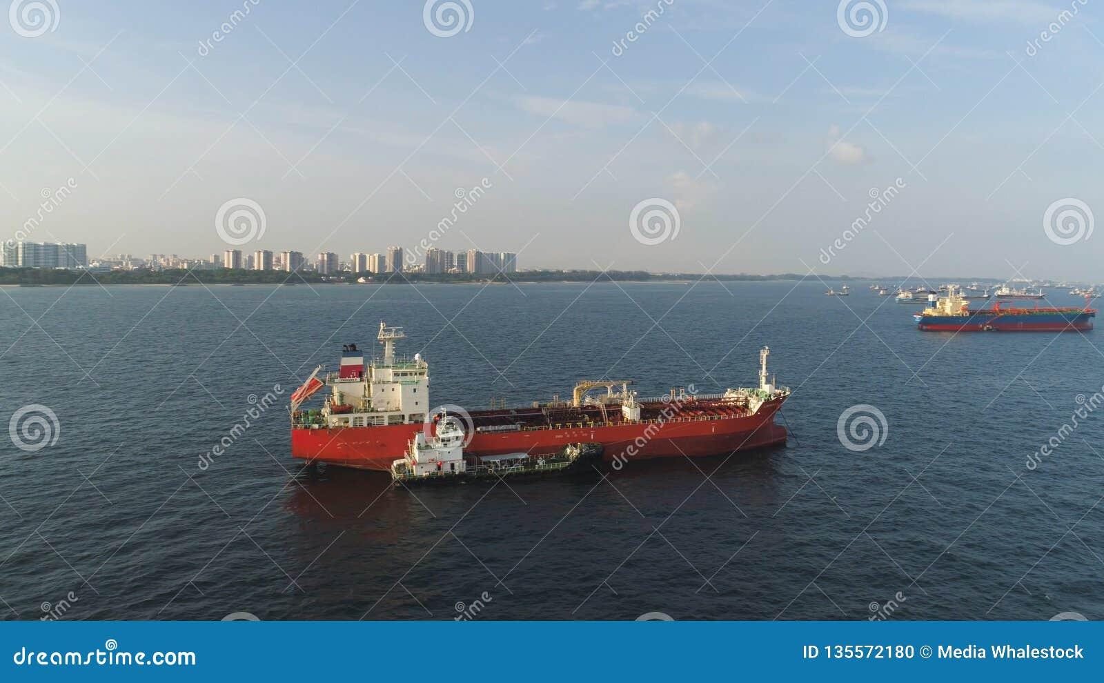 Viele Frachtschiffe, die in das Meer im sonnigen Wetter auf Hintergrund des blauen Himmels segeln schuß Lastkähne, die in die Was