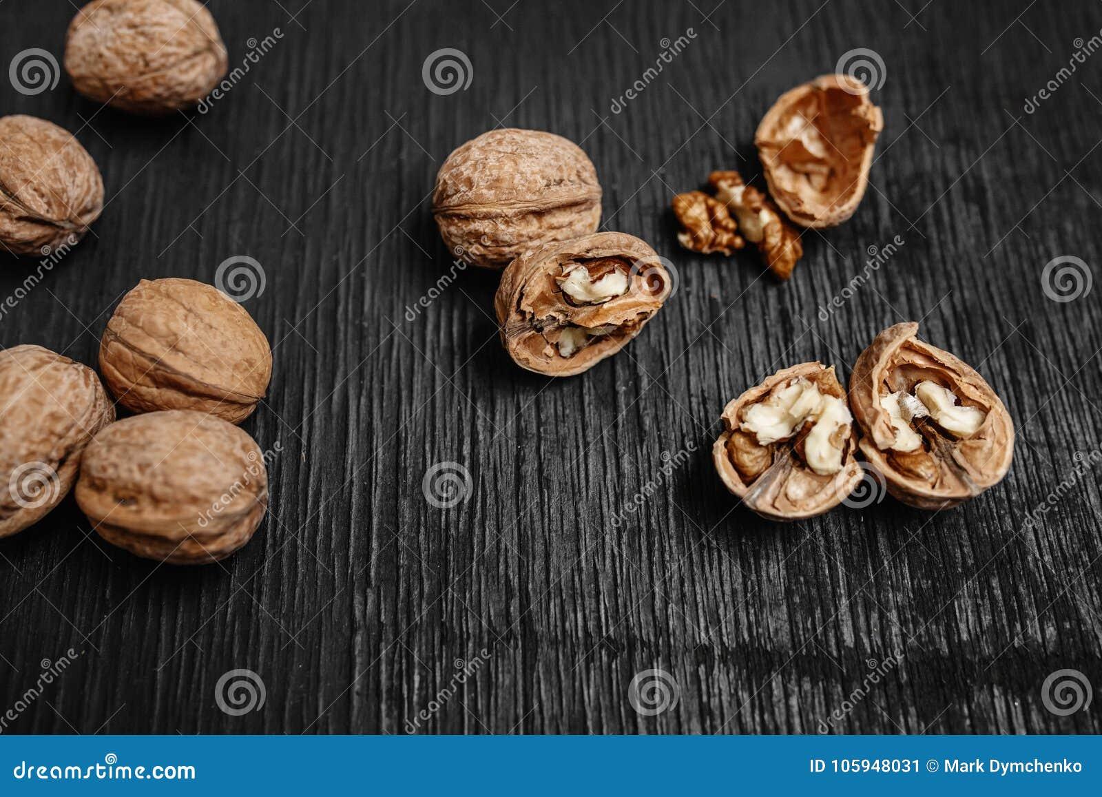 Viele frische Nüsse auf einem schwarzen hölzernen Hintergrund Optimale Verfahren für Designer