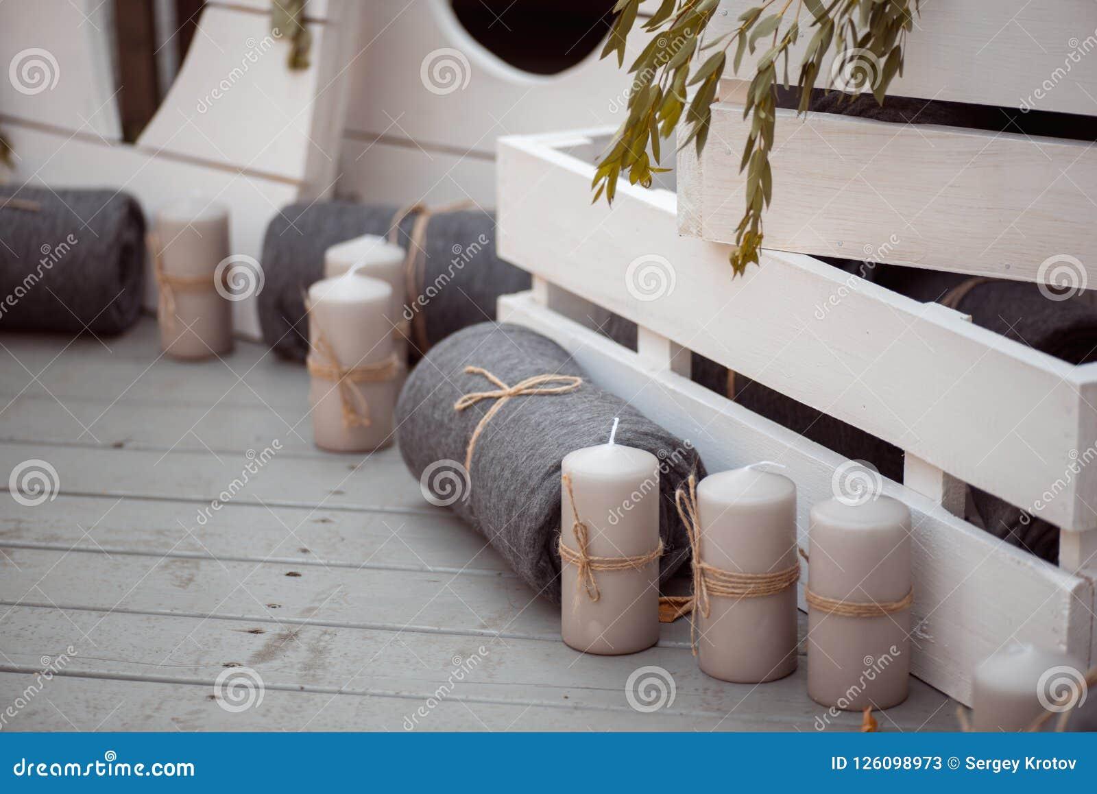 Viele Weiß gemalten hölzernen Käfigkästen, einige mit dekorativen Kerzen, rollten Decken und inländische Anlagen