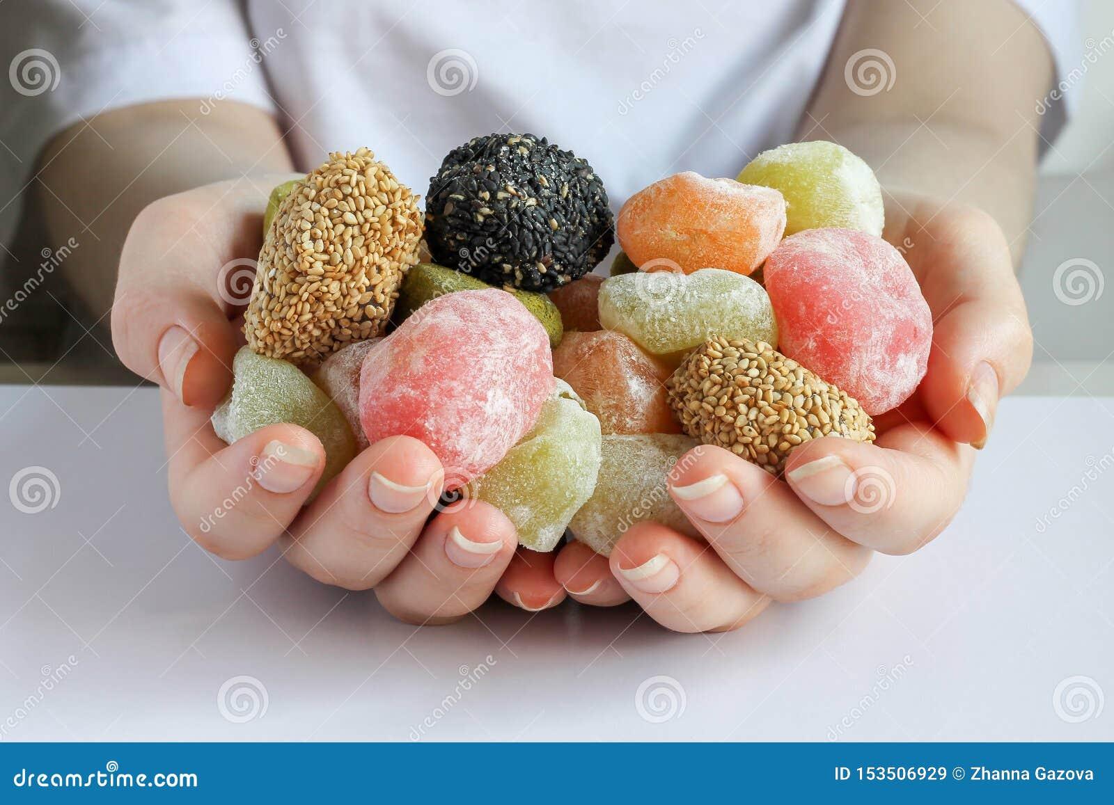 Viele weichen mehrfarbigen Süßigkeiten in zwei Händen