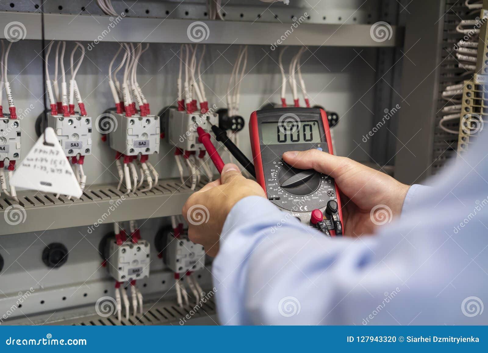 Vielfachmessgerät in den Händen der Elektrikernahaufnahme Halten Sie Arbeiten im elektrischen Kasten instand Wartung der elektris