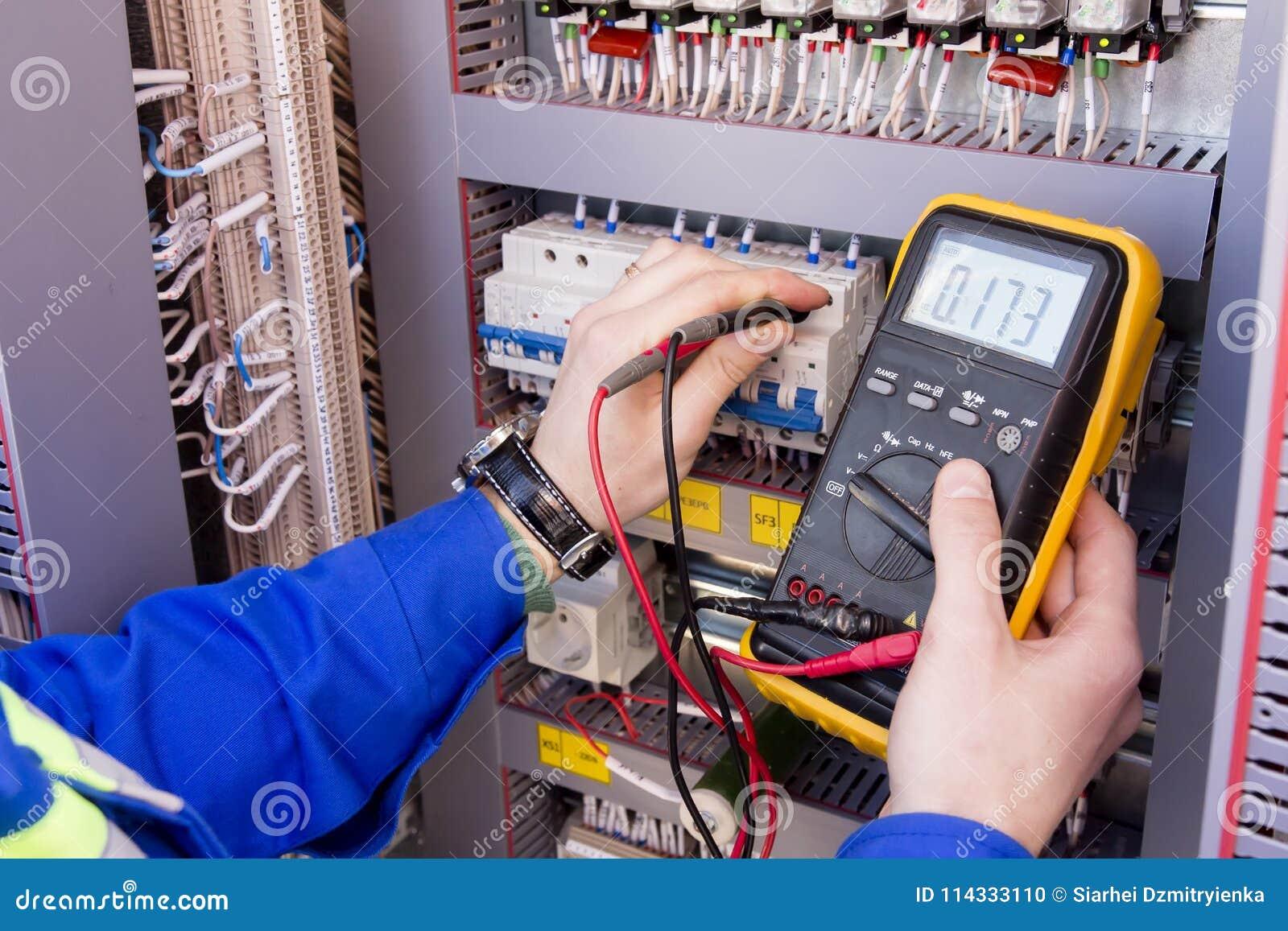 Vielfachmessgerät ist in den Händen des Ingenieurs im elektrischen Kabinett Anpassung des automatisierten Kontrollsystems für ind