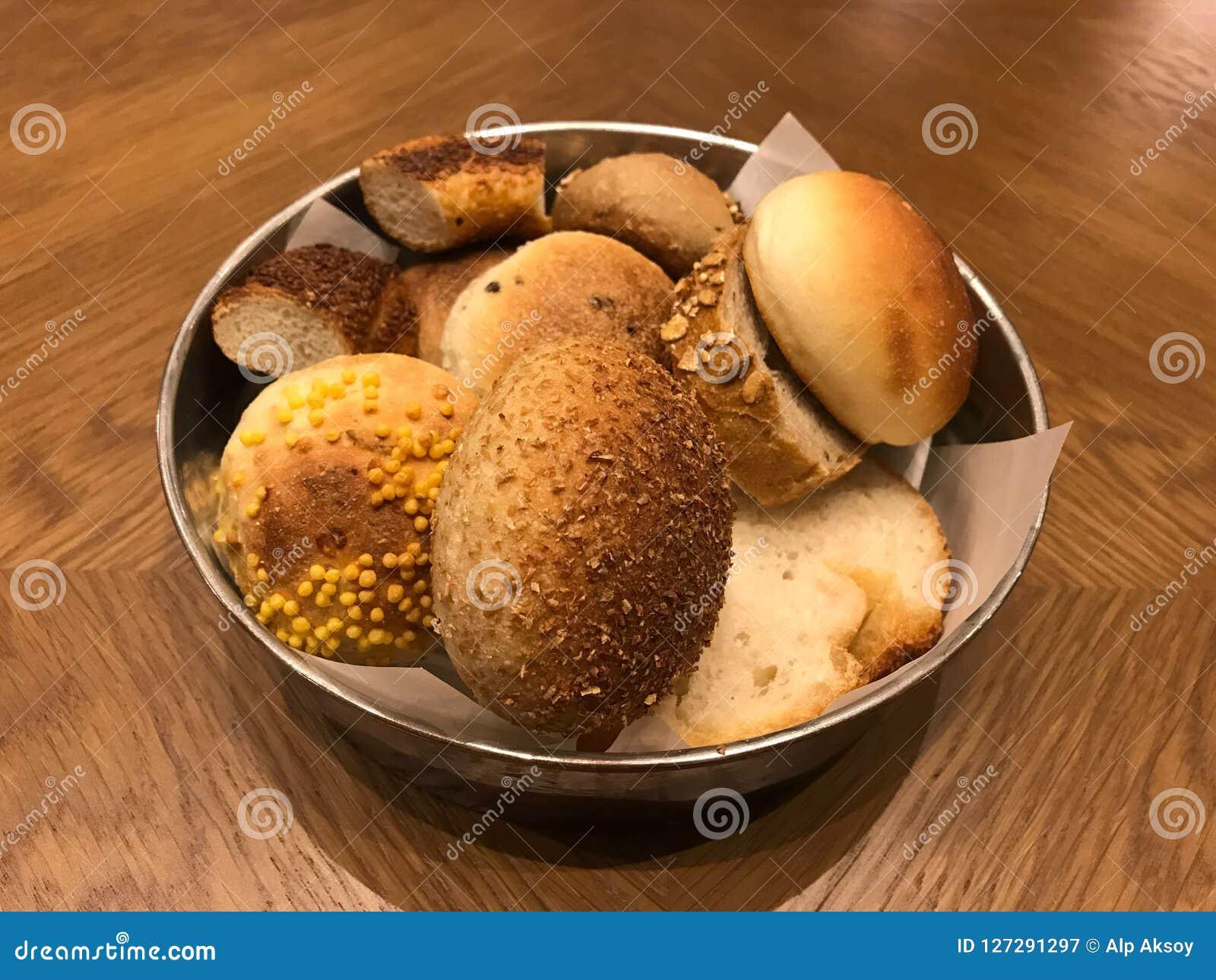 Vielzahl von kleinen Broten im Metallkorb auf Holzoberfläche