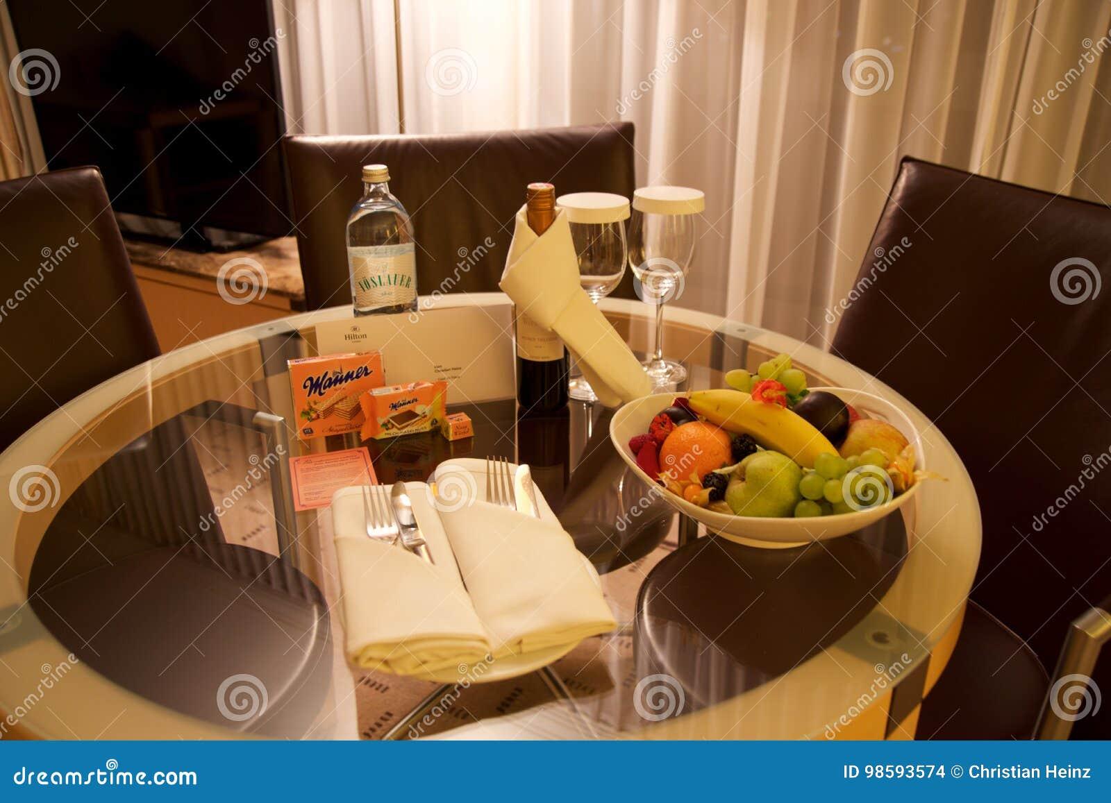 VIENA, AUSTRIA - 28 de abril de 2017: Tarde romántica con la botella de vino rojo, de dulces y de frutas en la habitación de lujo