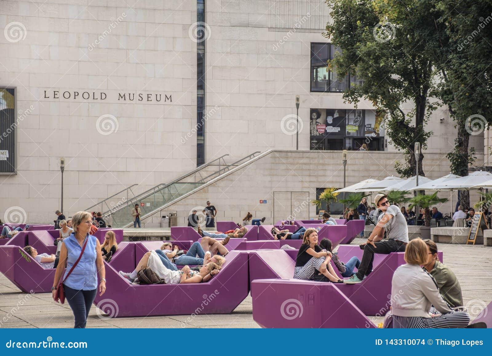 Viena, Austria - septiembre, 15, 2019: nTourists, pares jovenes, adolescentes y familias relajándose en los bancos del