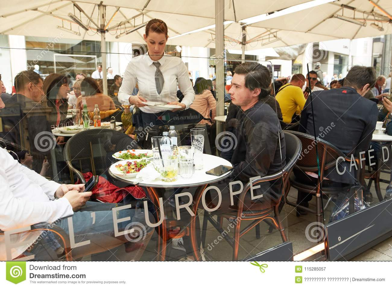Vienna, Austria - 15 April 2018: A street cafe. Waiter and visitors at tables.