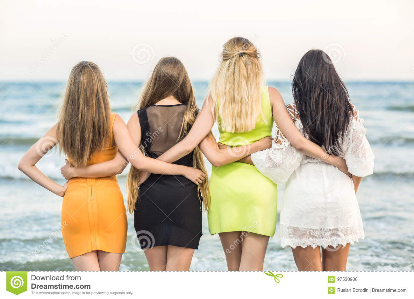 Vier aantrekkelijke jonge vrouwen die zich op een overzeese achtergrond bevinden Mooie dames` ruggen in heldere kleding Meisjes h