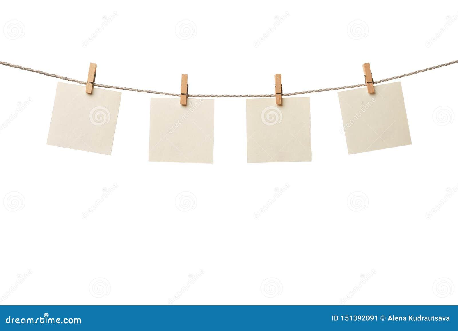 Vier alte leere Papieranmerkungen, die am Seil lokalisiert auf weißem Hintergrund hängen
