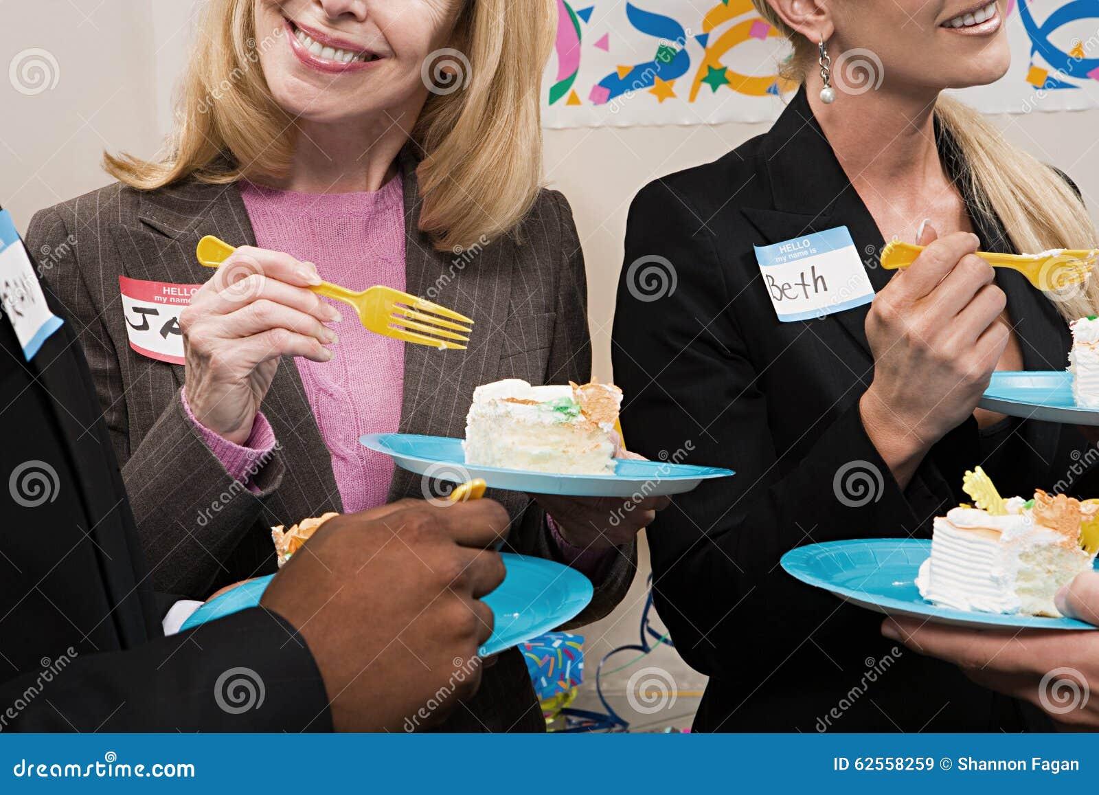 Vier Büroangestellte, die Kuchen essen