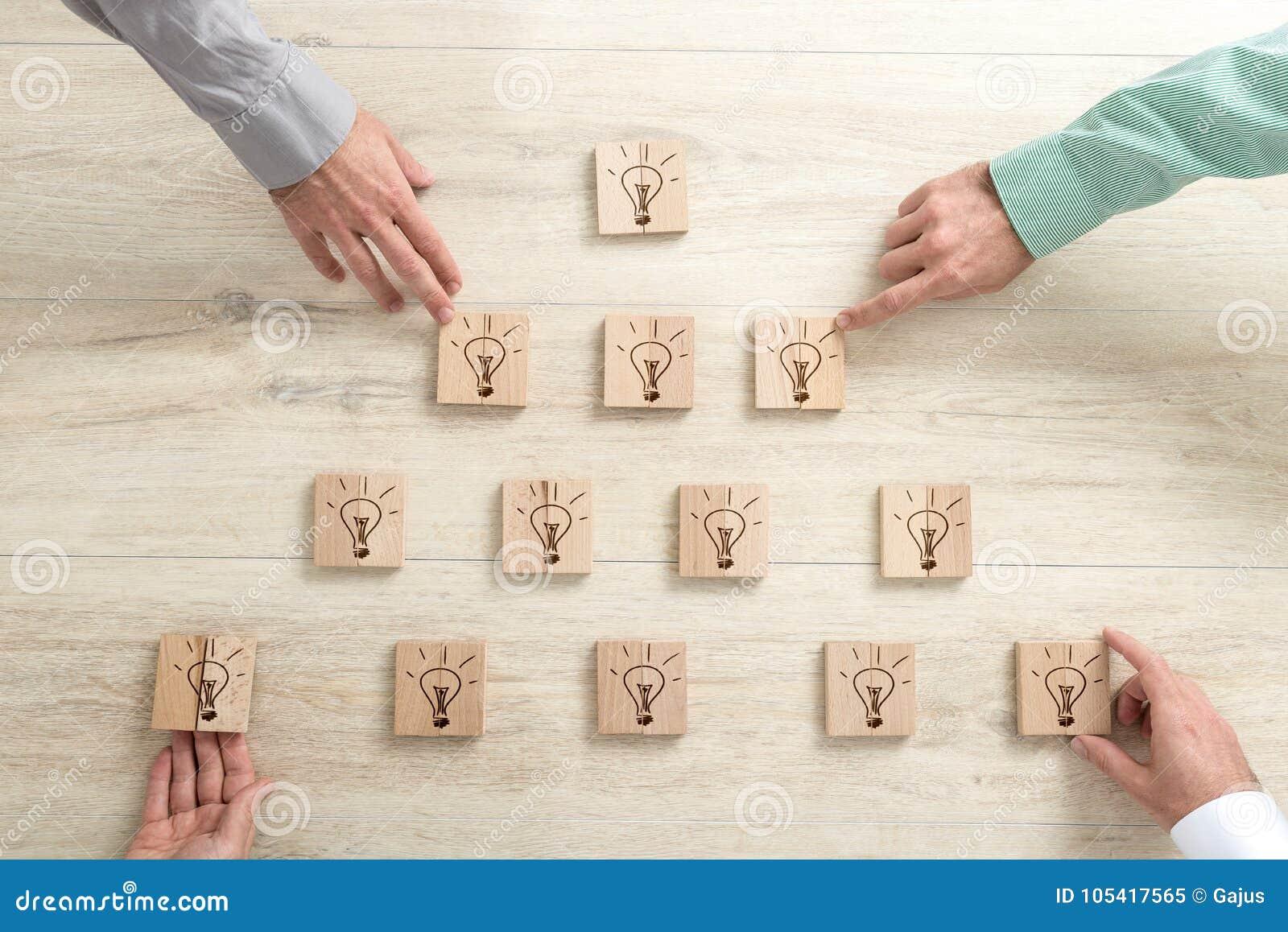Vier bedrijfsmensen die houten blokken met gloeilampen plaatsen in a