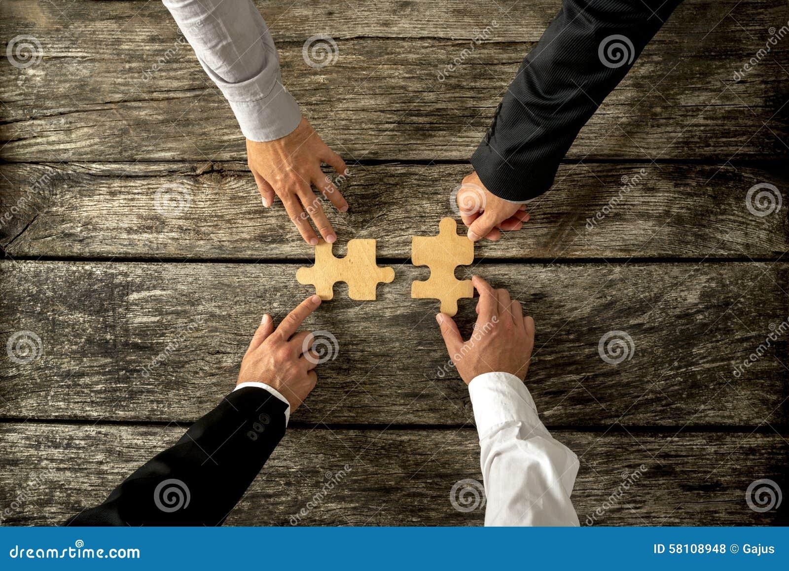 Vier erfolgreiche Geschäftsleute, die Puzzlespiel zwei sich anschließen, bessert jedes bein aus