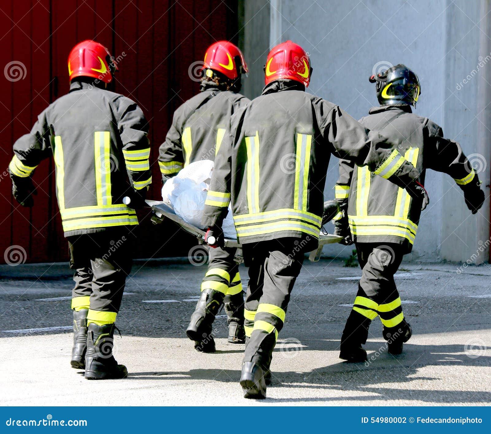 Vier Feuerwehrmänner in der Aktion tragen eine Bahre