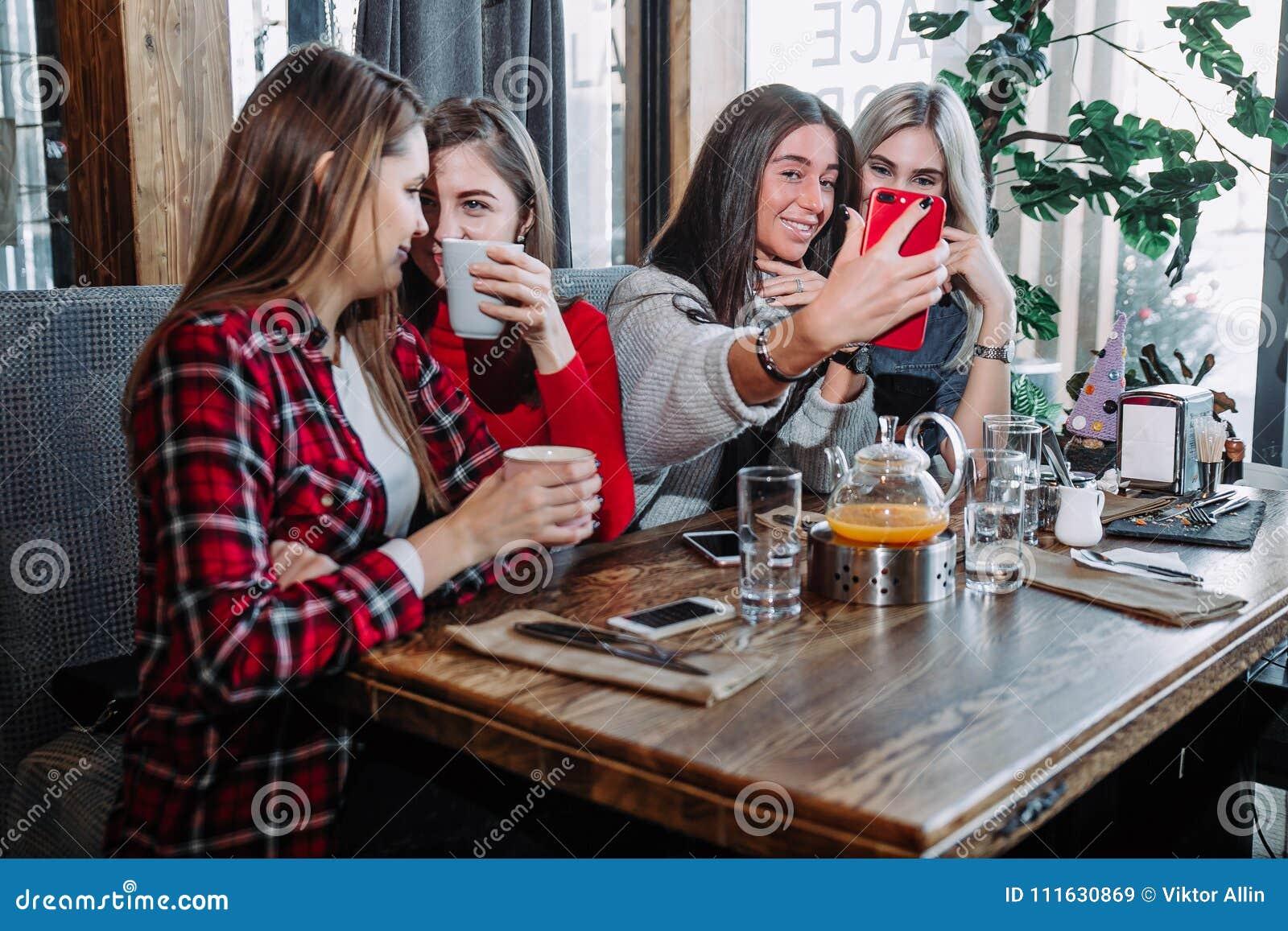 Vier Freundinnen, die bei der Unterhaltung am Café genießen