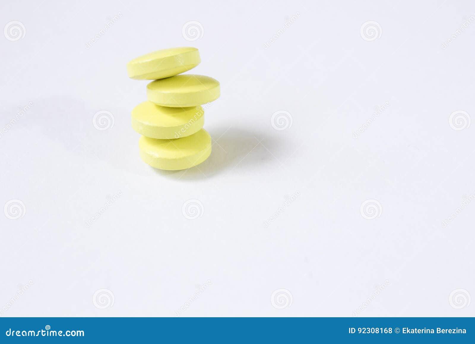 Vier gele tabletten worden gestapeld bovenop elkaar Witte achtergrond