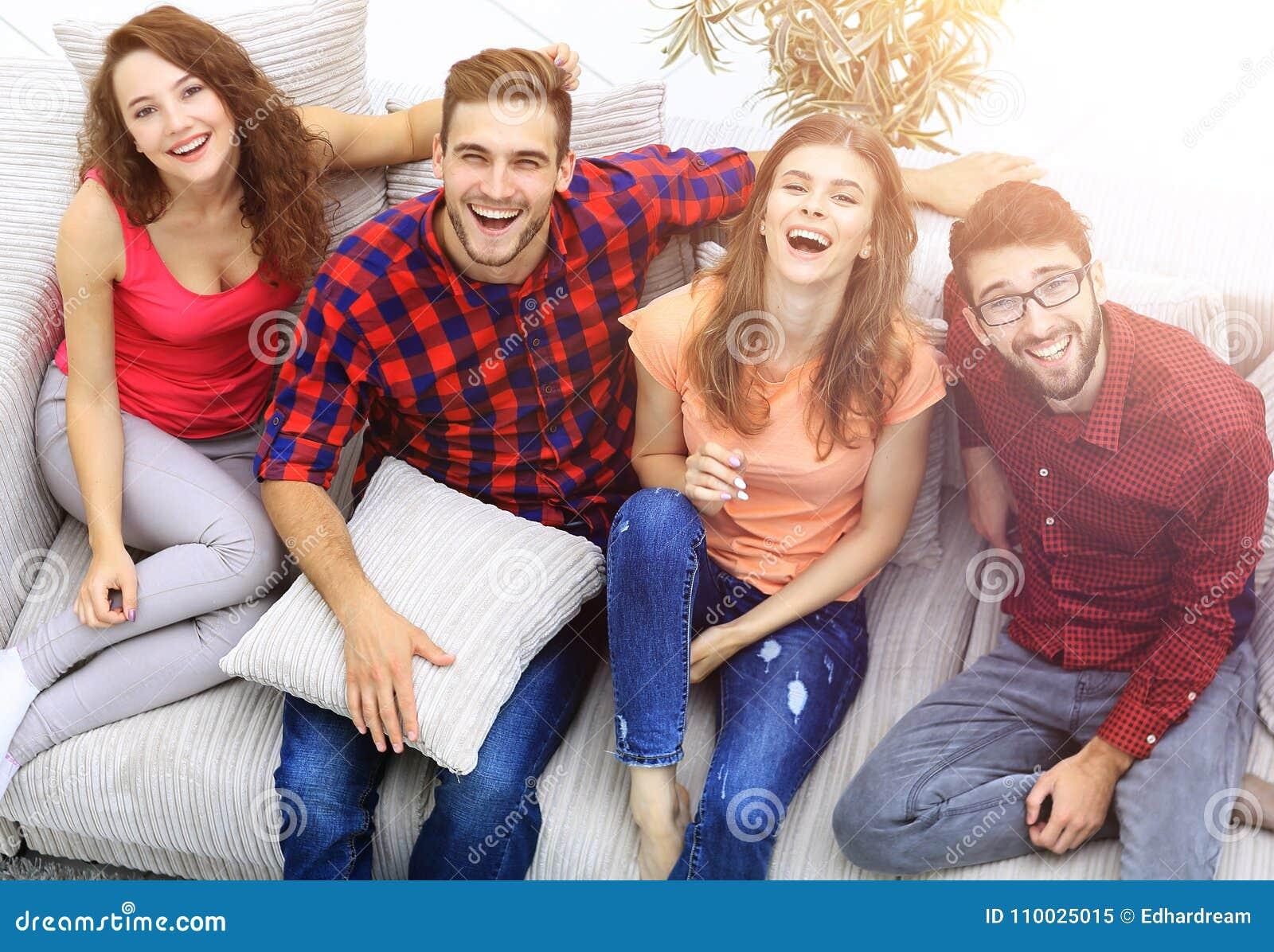 Vier gelukkige vrienden die terwijl het zitten op de laag lachen