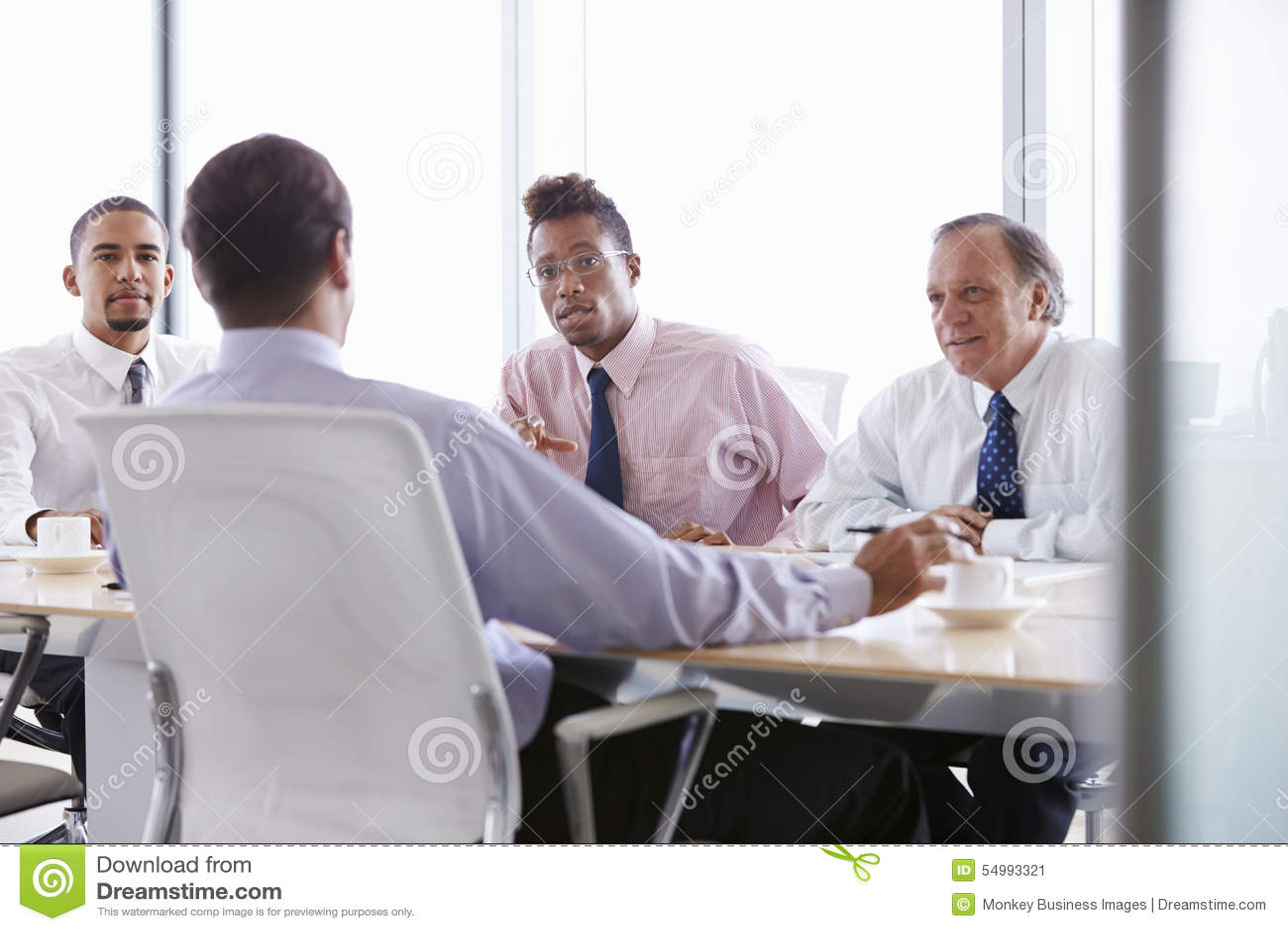 Vier Geschäftsmänner, die Sitzung um Sitzungssaal-Tabelle haben