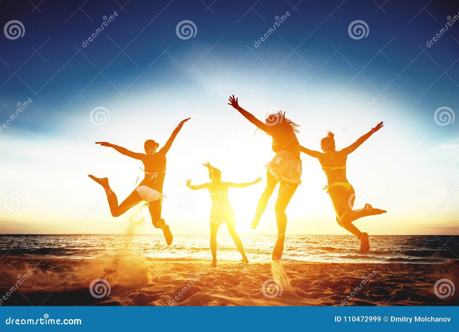 Vier glückliche Mädchen laufen und springen gegen Sonnenuntergangmeer