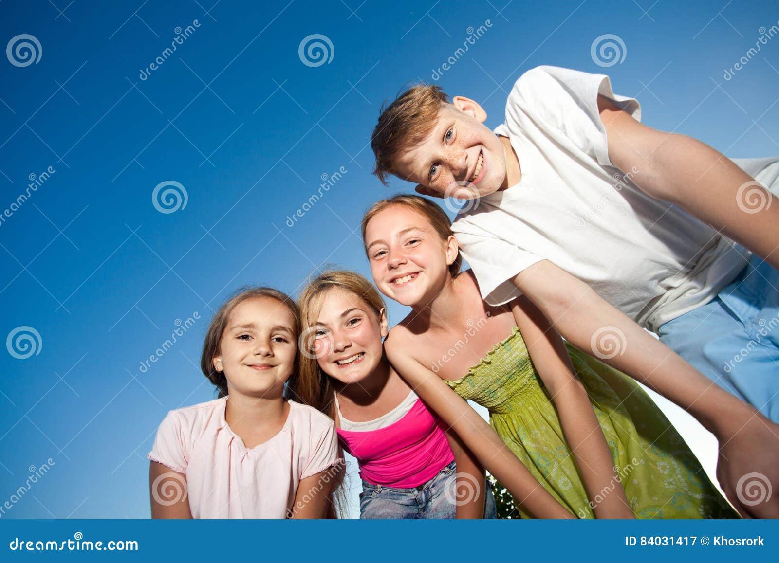 Vier glückliche schöne Kinder, die Kamera von der Spitze am sonnigen Sommertag und am blauen Himmel betrachten Betrachten der Kam