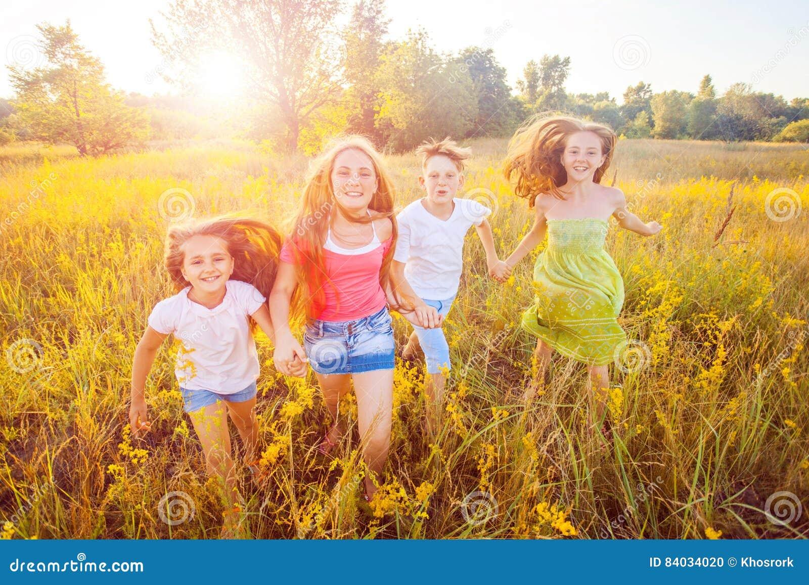Vier glückliche schöne Kinder, die am schönen Sommertag zusammenrücken spielend laufen